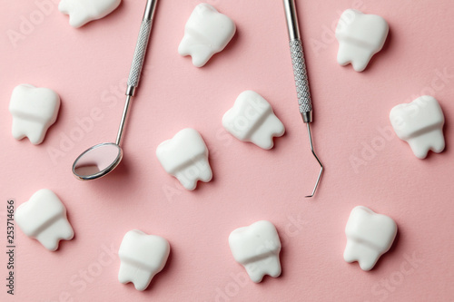 Healthy white teeth pink background and dentist tools mirror, hook.