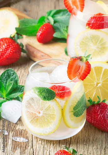 Summer iced lemonade with strawberries, lemon, mint and soda, vintage wood background, selective focus - 253715258