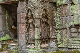 Relief of apsaras and false windows with balusters in Ta Prohm temple, Cambodia