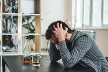 """Постер, картина, фотообои """"The most common way people give up their power is by thinking they don't have any. Drunk man with glass and bottle of whiskey sitting at table in kitchen. Drinking alone. Male alcoholism concept"""""""