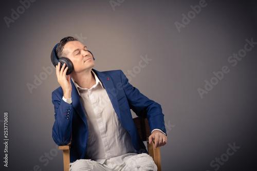 Relaxed businessman listening music on headphones. - 253770608