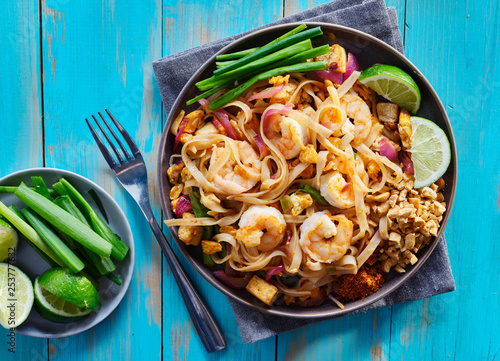 shrimp pad thai on plate in flat lay composition with copy space atop of colorful wooden table - 253777632