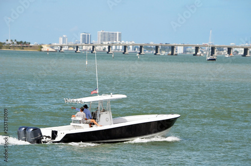 Small open sports fishing boat cruising the Florida Intra-Coastal Waterway off Miami Beach