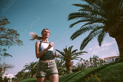 the girl is engaged in morning jogging among palm trees in a respectable suburb area.