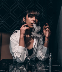 brunette smokes in a bar under the lamp
