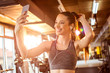 Leinwanddruck Bild - Smiling fitness girl with earphones using smartphone to take a selfie in the gym