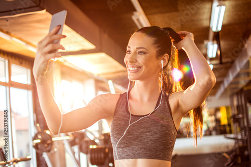 Leinwanddruck Bild Smiling fitness girl with earphones using smartphone to take a selfie in the gym