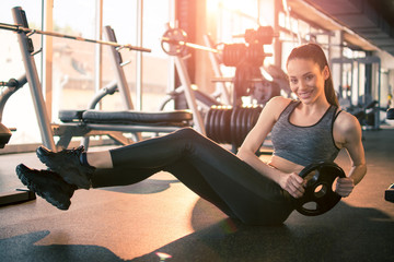 Sporty fit girl workout with weight plate in gym. Young woman in active-wear doing sit-ups with weight on the floor in fitness center