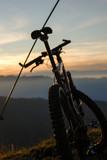 Mountainbiker auf Berggipfel im Sonnenuntergang.