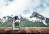 glass of water blurred mountains background