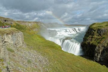Touristen betrachten den Regenbogen über dem Wasserfall Gullfoss, Island
