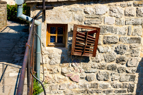 Authentic, stone wall, with beautiful, old, wooden shutters and window, minimal style, bright colors, background. © Natallia
