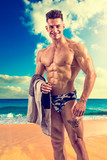 Handsome young man standing on a beach shirtless wearing bathing suit, showing muscular fit body