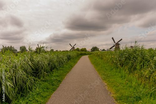Netherlands, kinderdijk, a path with windmill on the side of a road