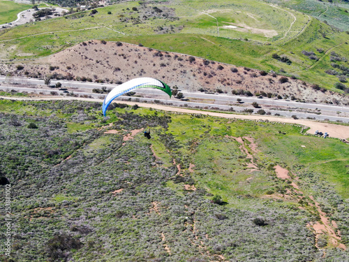 Para-glider over the top of the mountain during summer sunny day. Para-glider on the para-plane, strops -soaring flight moment flying over Black Mountain in San Diego, California. USA. © bonandbon