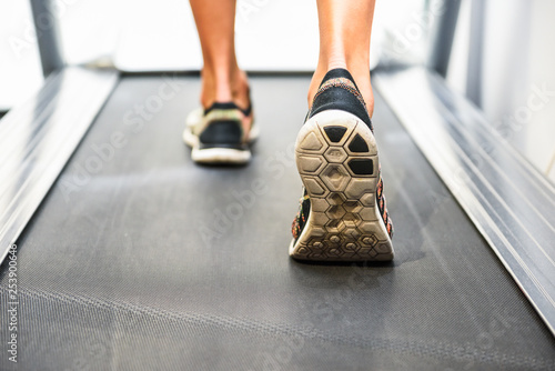 Male muscular feet in sneakers running on the treadmill at the gym. - 253900646