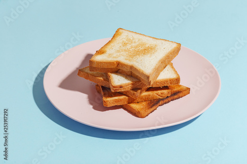 Leinwanddruck Bild Plate with toasted bread on light-blue background.