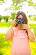 Leinwanddruck Bild - Young female photographer with a retro camera and smiling