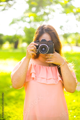 Leinwanddruck Bild Young female photographer with a retro camera and smiling