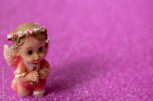 Angel figurine, toy on a pink background.. Selective focus. Space to the right for lettering or design. Close up. - 253930292