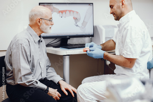 Leinwanddruck Bild Handsome old man talking to the dendist. Two man in the dentist's office