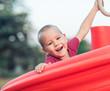 Leinwanddruck Bild - Little smiling boy on a slide