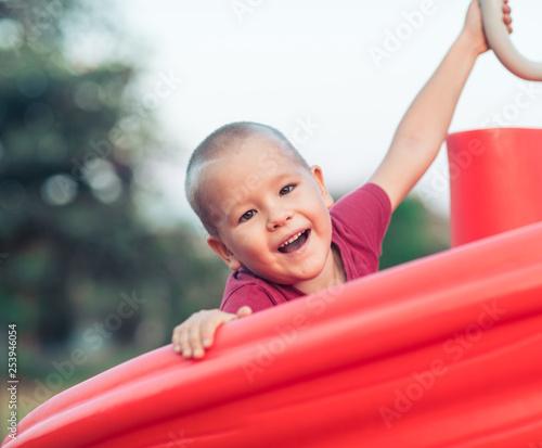 Leinwanddruck Bild Little smiling boy on a slide