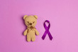 Children's toy with a Purple epilepsy awareness ribbon on a purple background. World epilepsy day.