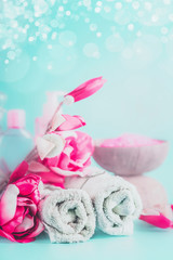 Spa towels with pink flowers at light blue background with bokeh. Beauty concept