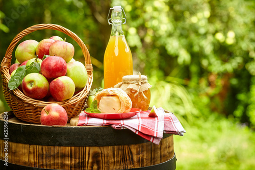 apples on background orchard standing on a barrel. Apple juice and apple preserves. - 253966254