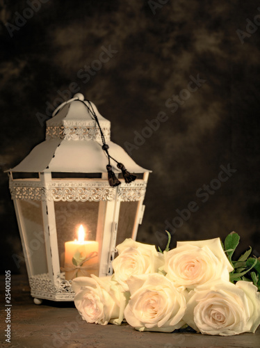 Beautiful white roses and candle on table against black background © Bera_berc