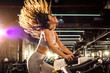 Leinwanddruck Bild - Side view of attractive young woman with long hair in the air during during cycling training in gym