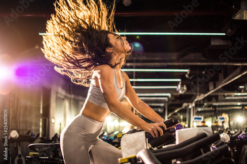 Leinwanddruck Bild Side view of attractive young woman with long hair in the air during during cycling training in gym