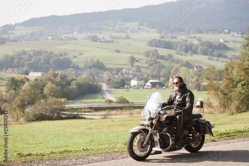 Long-haired bearded cool biker in sunglasses and black leather clothing riding modern cruiser motorcycle along sunny asphalt road on bright summer day on background of green rural misty landscape.