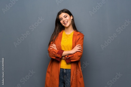 Leinwanddruck Bild Teenager girl with coat over grey wall keeping the arms crossed in frontal position