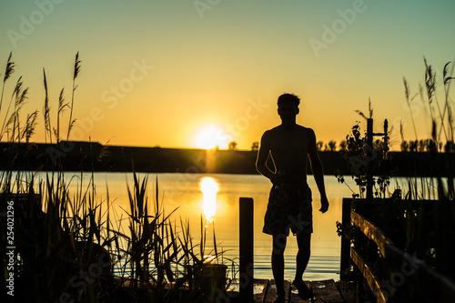 obraz PCV Postać przy zachodzie słońca