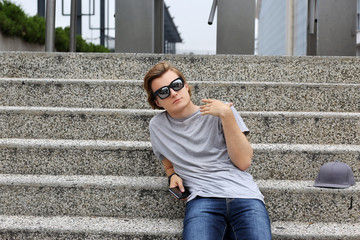 Teenager sitting on a city street