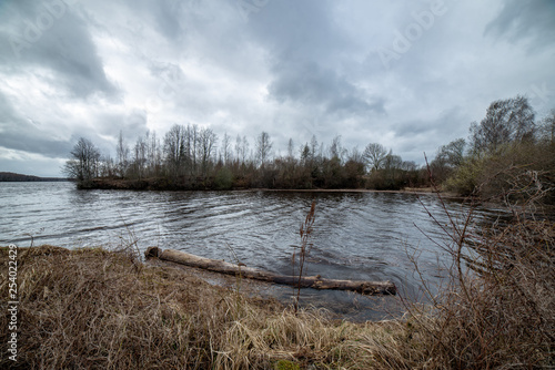 riverside landscape in latvia with dark water and dirty shore line - 254022429