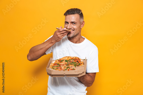 Image of joyful man 30s in white t-shirt holding and eating pizza while standing isolated