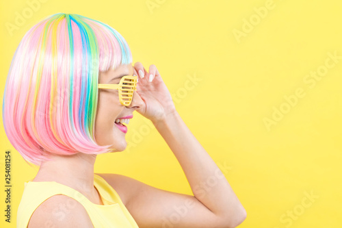 Young woman in a colorful wig with shutter shades sunglasses on a yellow background