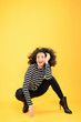 Fun African American Woman Squatting on a Yellow Background