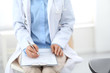Female doctor writing up medication history records form on clipboard, while sitting at the chair. Physician at work in hospital or clinic. Healthcare, insurance and medicine concept