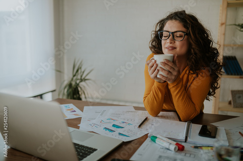 Beautiful young designer taking a coffee break at her desk. Enjoying the smell of the fresh coffee. The work can wait.