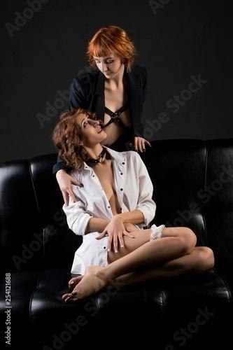 Provocative sensual women on black leather sofa - 254121688