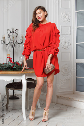 Gorgeous stylish girl dressed in the fashionable red dress poses in the room next to the white door