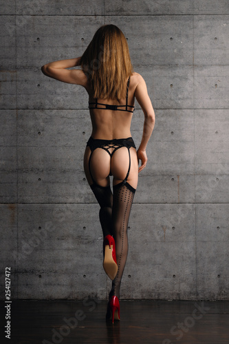 Back view of beautiful woman in black lingerie, stockings with belt and red high heel shoes. One leg up.