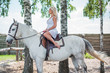 Woman with a white horse in a farm. Concept of animals and human. Spring - summer season, hobby time