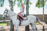 Fototapeta Konie - Woman with a white horse in a farm. Concept of animals and human. Spring - summer season, hobby time  © T.Den_Team