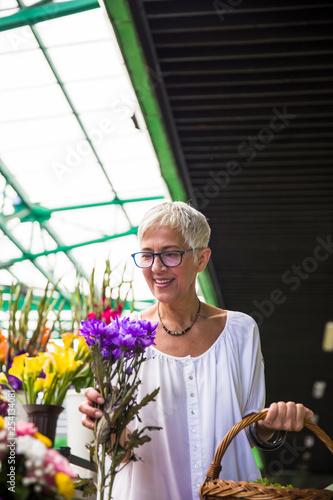 Leinwanddruck Bild Charrming senior woman buying  flowers on  market