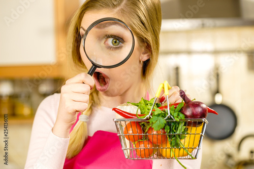 Woman investigating shopping backet with vegetables